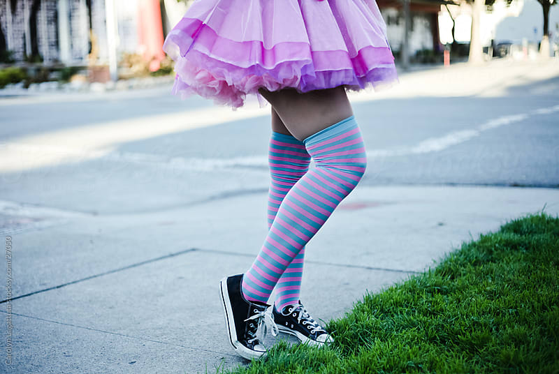 Girls legs with a striped tutu, knee-highs and tennis shoes. by Carolyn Lagattuta for Stocksy United