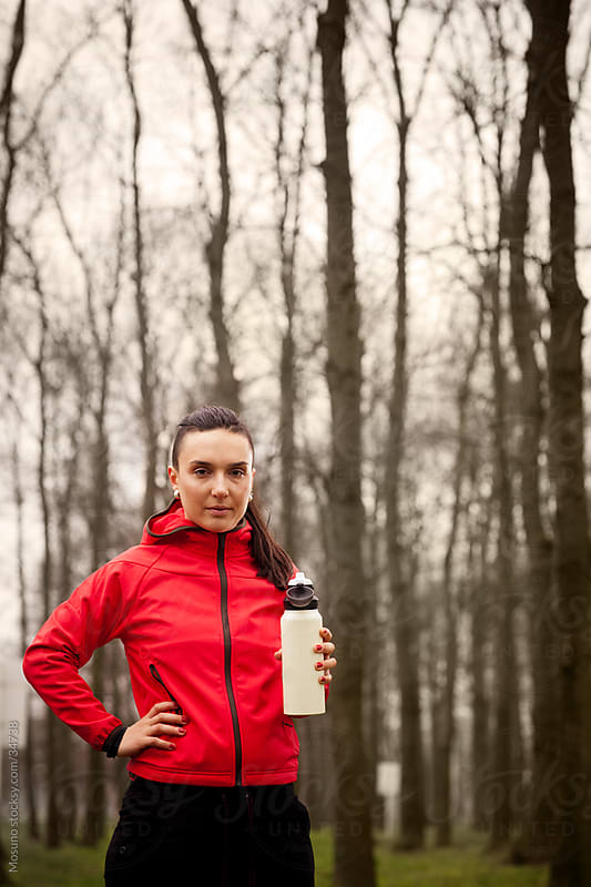 Woman standing with a bottle of water after jogging in the park.  by Mosuno for Stocksy United