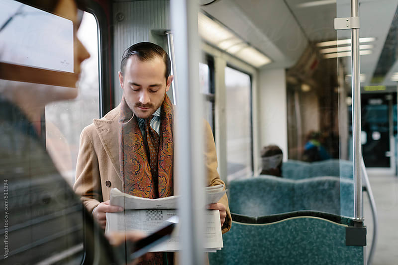 Businessman Reading Newspaper in Train by VegterFoto for Stocksy United
