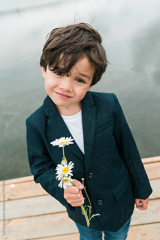 little boy with attitude and an offering of flowers by Tara Romasanta for Stocksy United