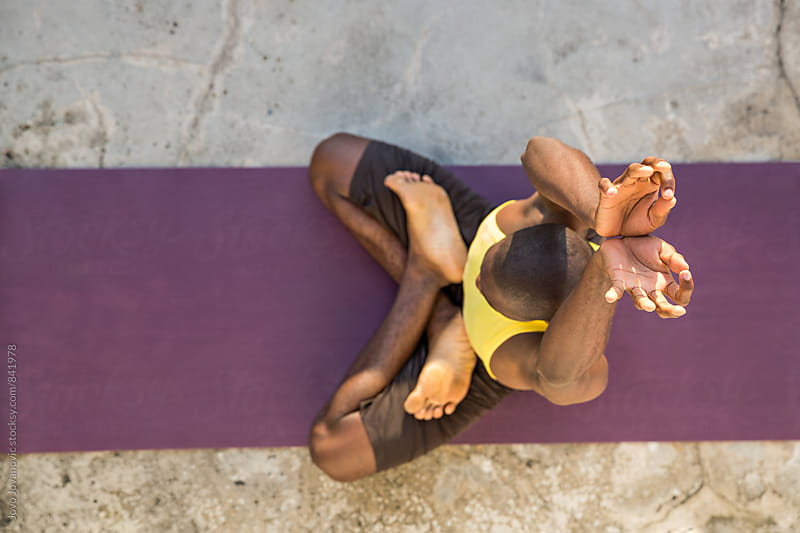 Yoga practitioner extending his hands upwards during an exercise  by Jovo Jovanovic for Stocksy United