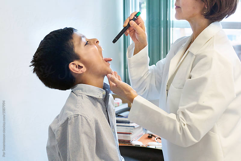 Pediatrician examining boy's throat with penlight by Per Swantesson for Stocksy United