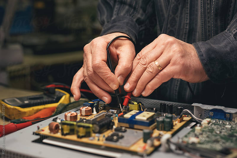 Technician probing a circuit board by RG&B Images for Stocksy United