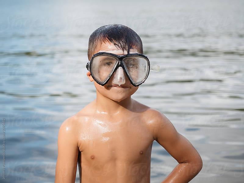 Skinny young child wearing scuba mask standing in front of lake water by Jeremy Pawlowski for Stocksy United