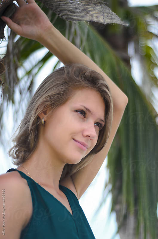 Young pretty lady portret nearby palm tree by Alice Nerr for Stocksy United