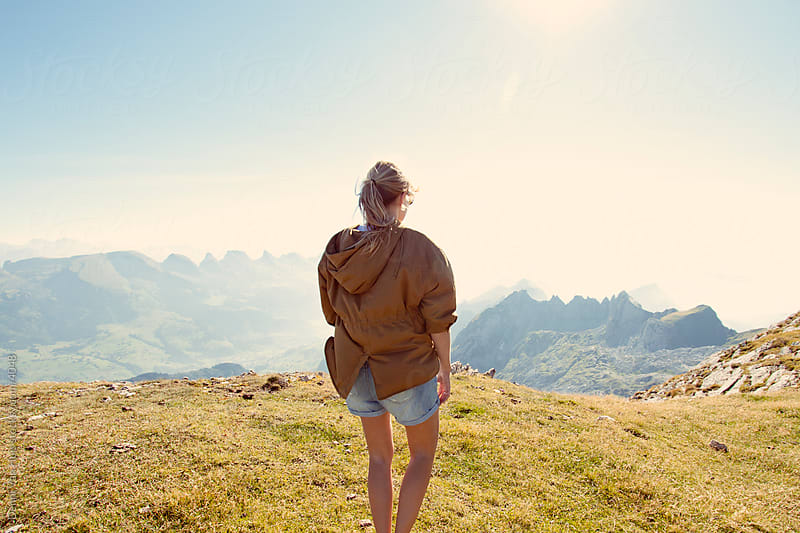 Young woman standing on top of a mountain and enjoying the view by Denni Van Huis for Stocksy United