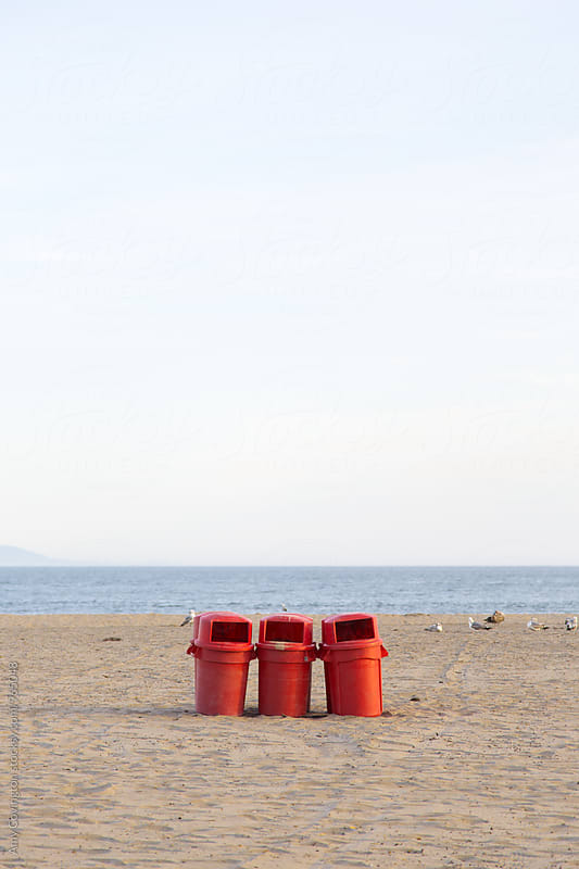 Red trash cans on a beach by Amy Covington for Stocksy United