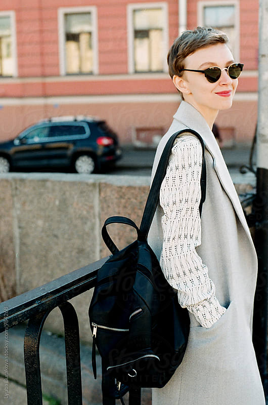 Young woman with backpack on the street by Lyuba Burakova for Stocksy United