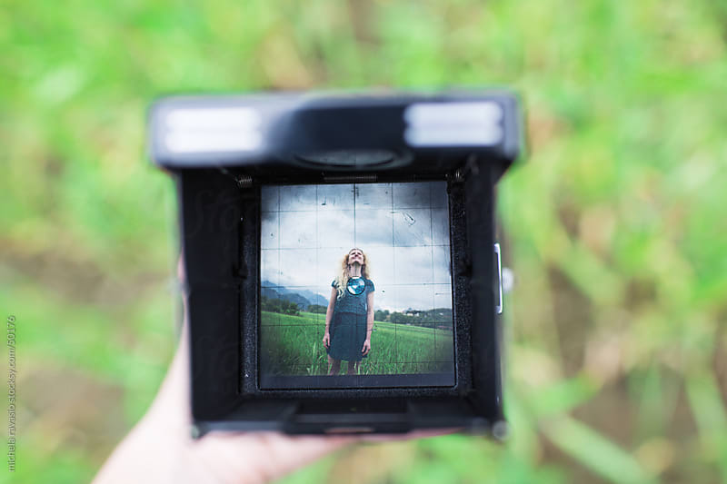 Woman looking up in a viewfinder go vintage camera by michela ravasio for Stocksy United