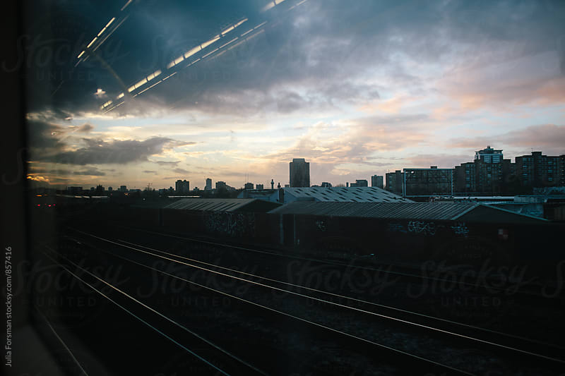 View from a train window in London at dusk. by Julia Forsman for Stocksy United