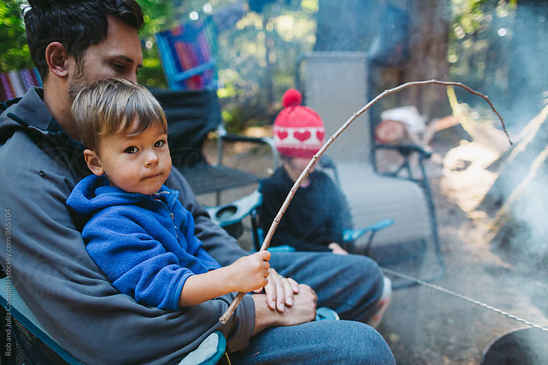 Father and son roasting marshmallow together  by Rob and Julia Campbell for Stocksy United