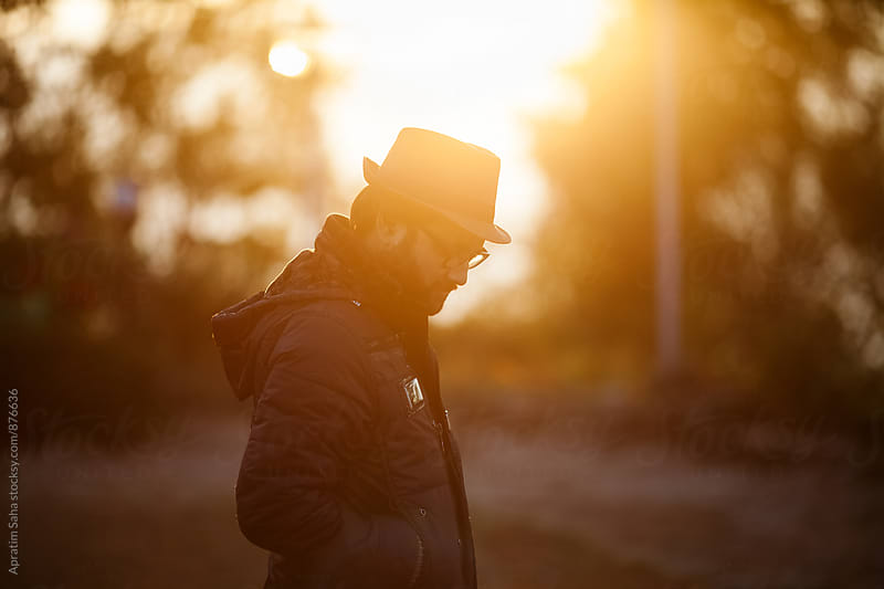 Outdoor portrait of a young handsome man against sun  by Apratim Saha for Stocksy United
