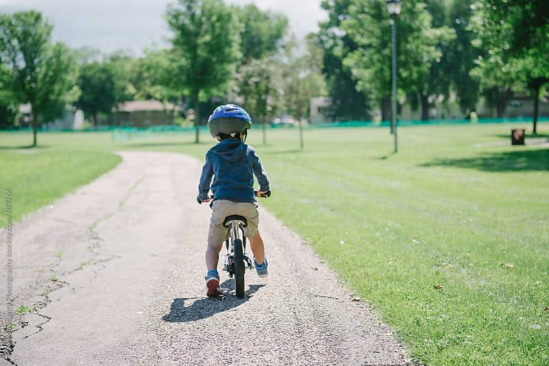 boy on a balance bike glides down a bike path by Tara Romasanta for Stocksy United