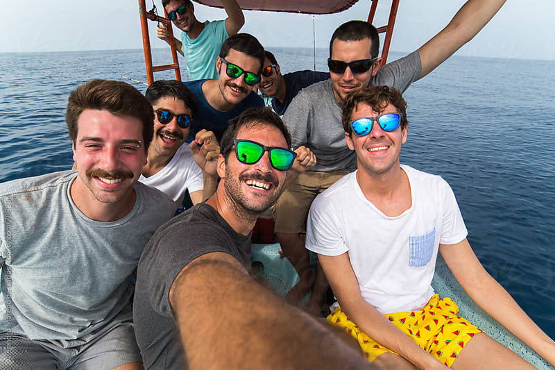 Group of happy excited young men taking a selfie picture during a boat trip in the sea by Alejandro Moreno de Carlos for Stocksy United
