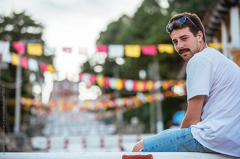 Young hipster man sitting looking back with flying flags from a festivity in the background by Alejandro Moreno de Carlos for Stocksy United