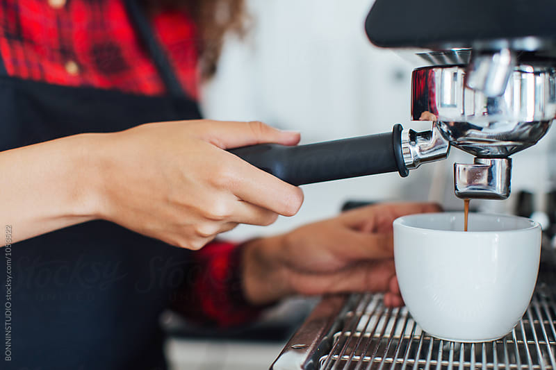 Closeup of young female barista operating coffee maker in cafe by BONNINSTUDIO for Stocksy United