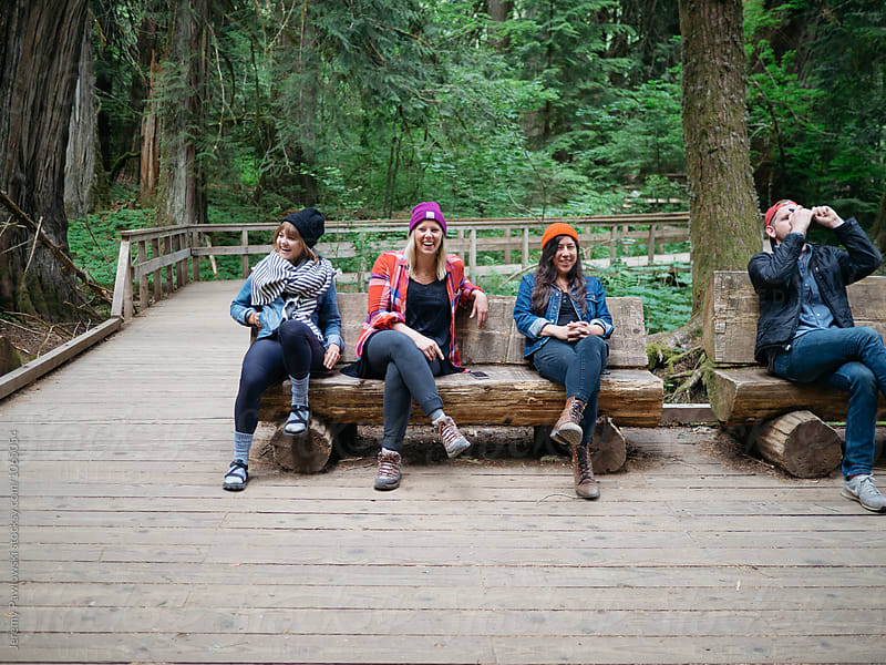 Group of hipster hikers sitting on wooden bench in forest by Jeremy Pawlowski for Stocksy United