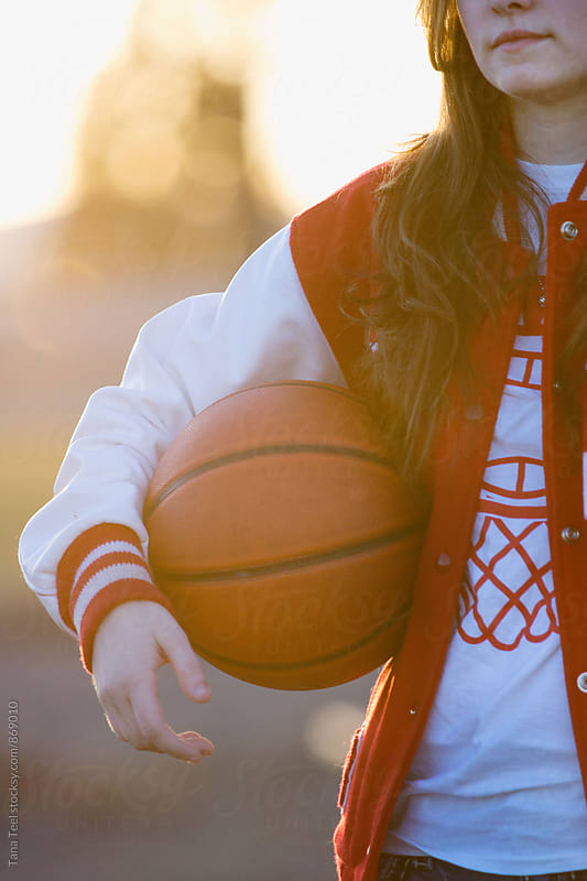 teen wearing letterman's jacket holds basketball by Tana Teel for Stocksy United