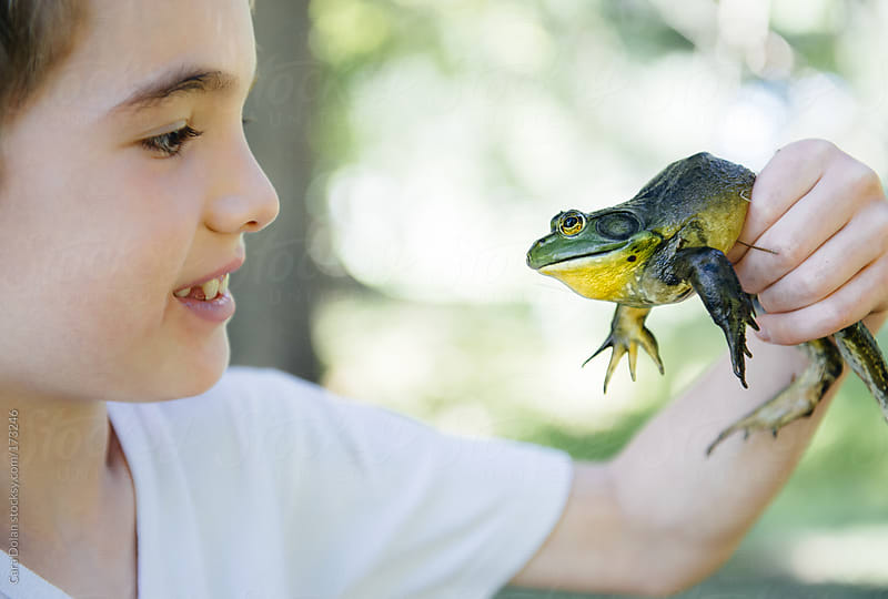 Boy looks at a frog he just caught in a pond by Cara Dolan for Stocksy United