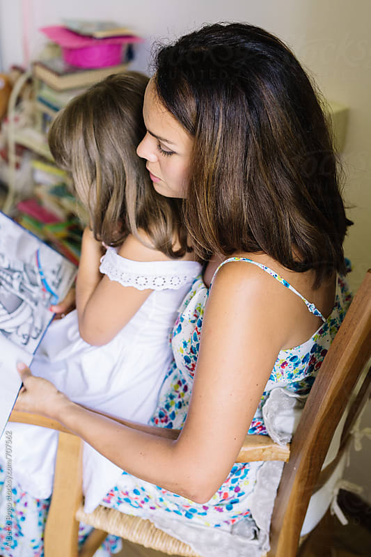 Mother and daughter reading a book together by Alberto Bogo for Stocksy United