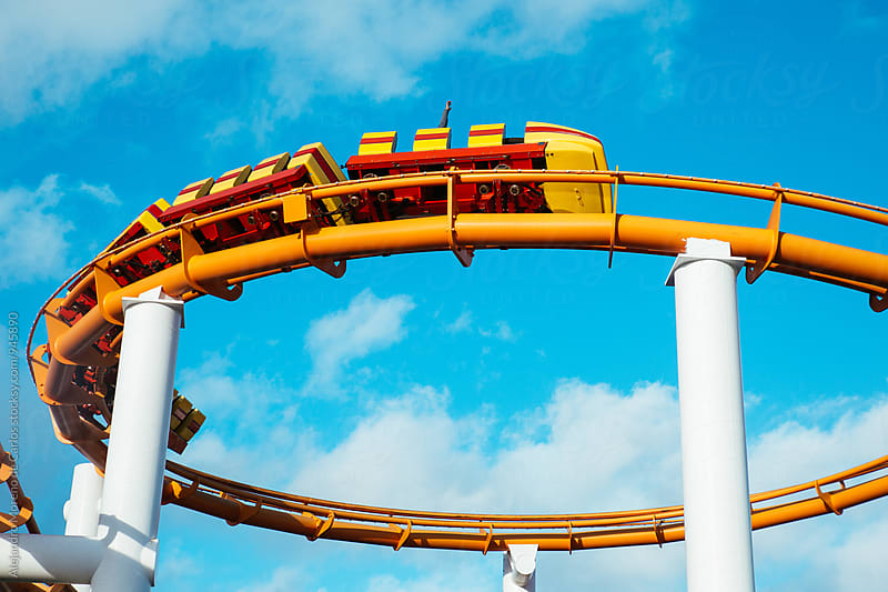 Rollercoaster against blue sky in a fair by Alejandro Moreno de Carlos for Stocksy United
