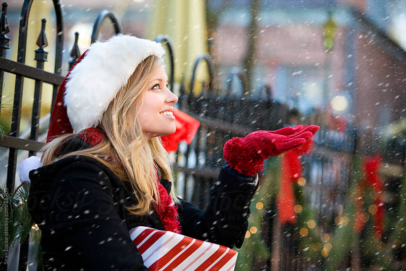Christmas: Woman Holds Out Hand to Catch Snow by Sean Locke for Stocksy United