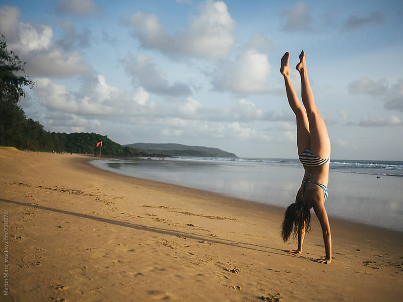 Fit girl doing handstand on the beach during sunset by Martin Matej for Stocksy United