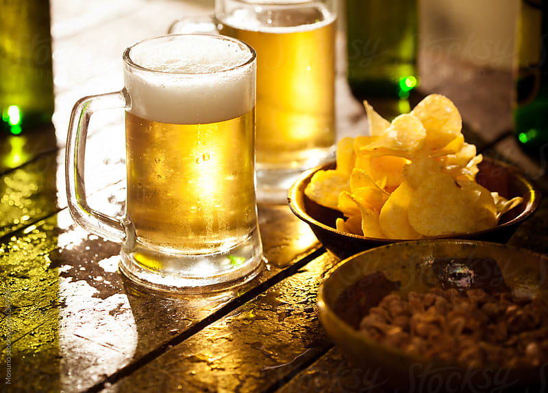 Beer and chips on the table. by Mosuno for Stocksy United