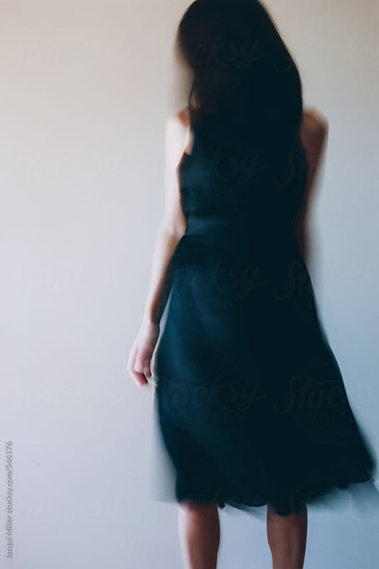 Unrecognisable woman moving in a flowing black dress by Jacqui Miller for Stocksy United