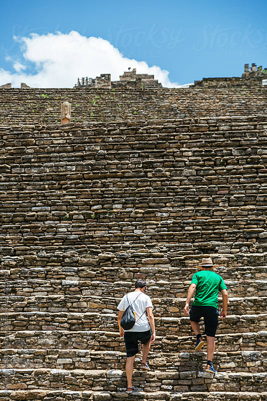 Two men going up the steep steps of ancient pre-columbian ruins by Alejandro Moreno de Carlos for Stocksy United