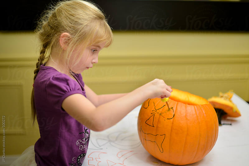 Little Girl Drawing Face on Halloween Jack-O-Lantern Pumpkin by JP Danko for Stocksy United