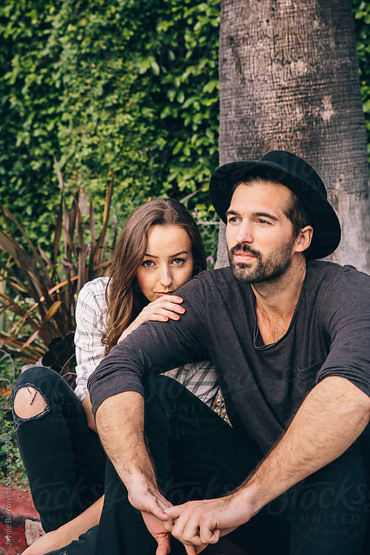 Young Couple Sitting in Front of Palm Trees by Jayme Burrows for Stocksy United