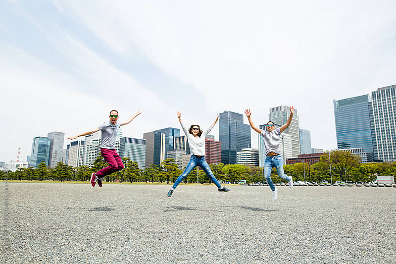 Portrait of young friends jumping in front of a Tokyo skyline. by BONNINSTUDIO for Stocksy United
