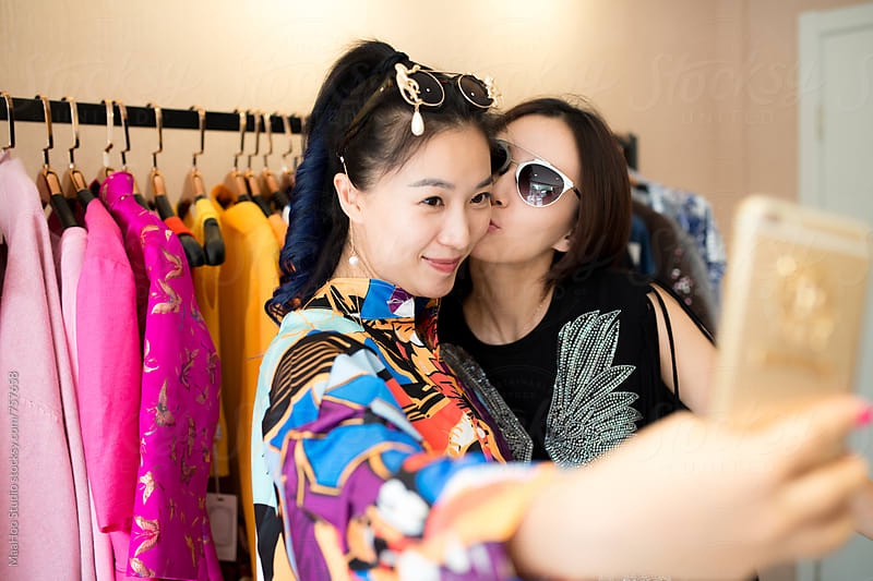 Two young woman taking selfie at clothing store by MaaHoo Studio for Stocksy United