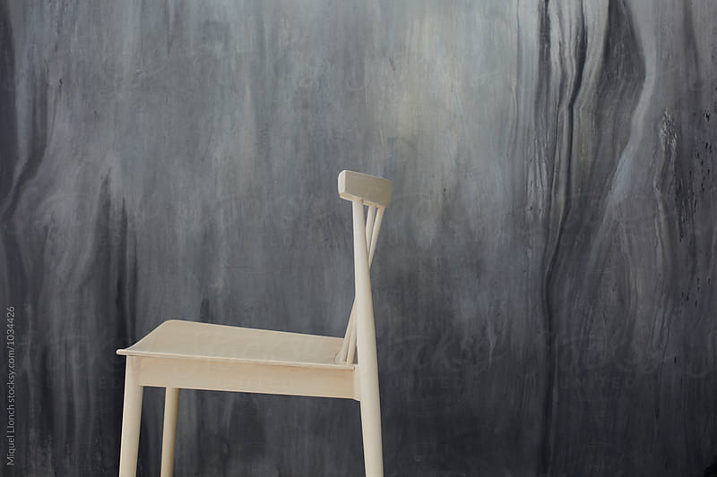 Design chair with abstract painting in the background by Miquel Llonch for Stocksy United