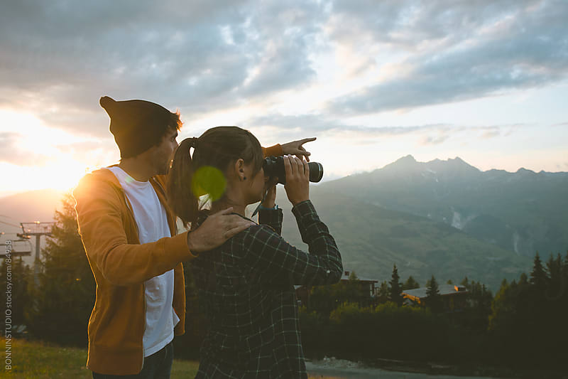 Cute cuple with binoculars on a beautiful sunset in les Alps, France. by BONNINSTUDIO for Stocksy United