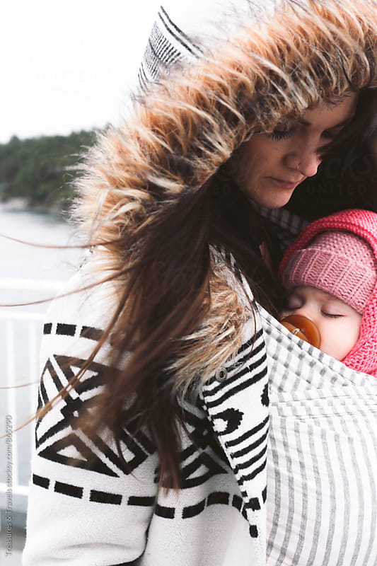 Woman holding her baby on a boat by Treasures & Travels for Stocksy United