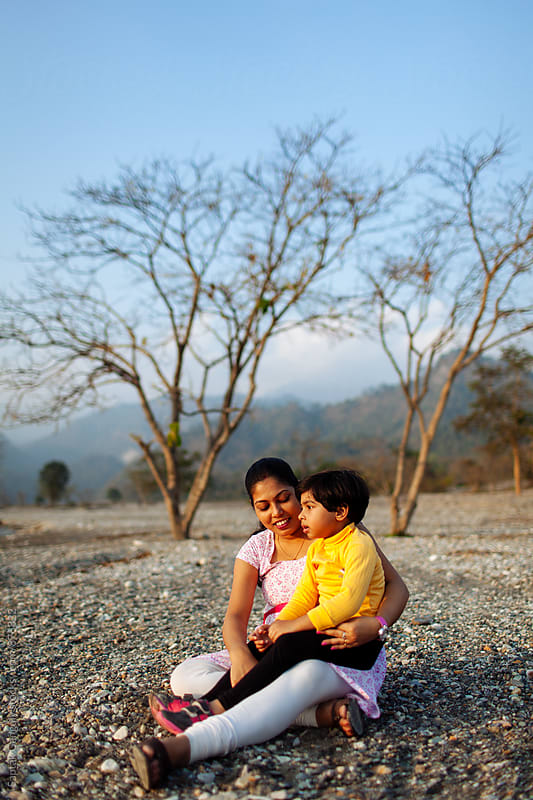Mother and daughter spending time together leisurely on a riverbed  by Saptak Ganguly for Stocksy United
