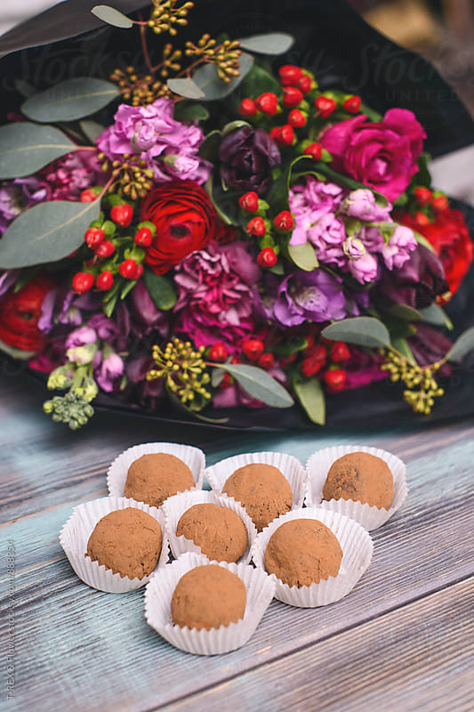 Delicious chocolate truffles against of bright bouquet by T-REX & Flower for Stocksy United
