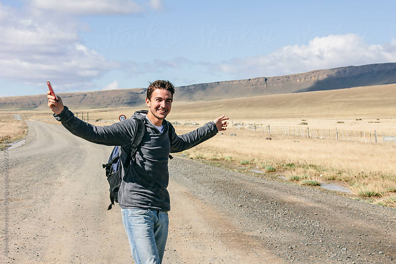 Young happy man on the middle of nowhere rising arms. Adventure travel by Alejandro Moreno de Carlos for Stocksy United