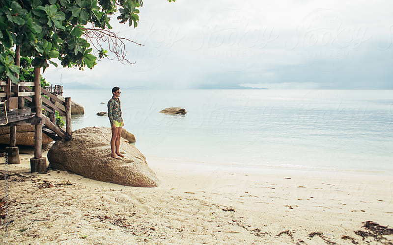 Young man standing on a rock looking out over beach and water  by Jovo Jovanovic for Stocksy United