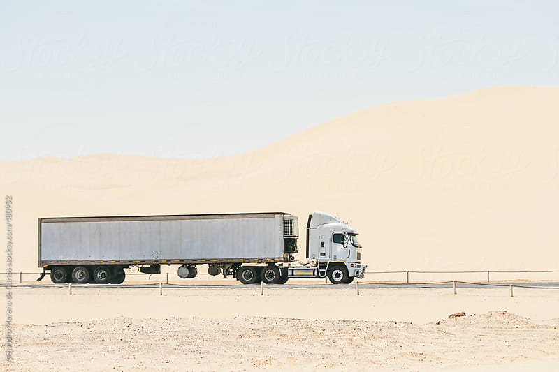 White cargo truck driving through the desert by Alejandro Moreno de Carlos for Stocksy United