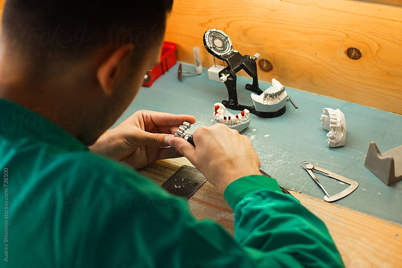 Orthodontist working on teeth denture in his workshop. by Audrey Shtecinjo for Stocksy United