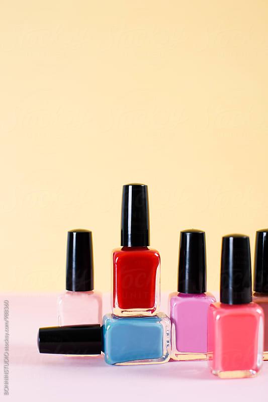 Set of nail polish bottles on colorful background. by BONNINSTUDIO for Stocksy United