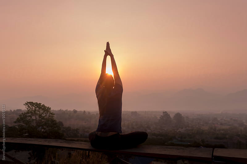 Woman doin yoga with view of rising sun over the mountains by Soren Egeberg for Stocksy United