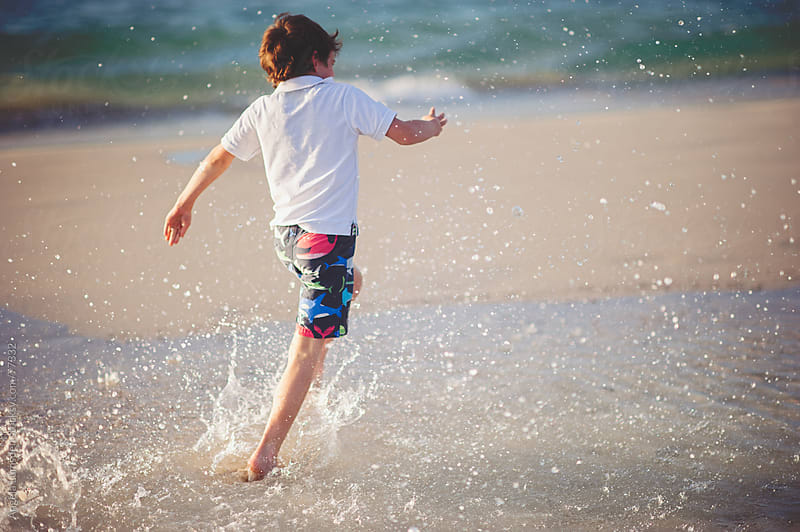 Boy splashing through water at the beach by Angela Lumsden for Stocksy United
