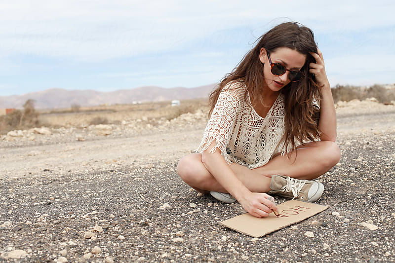 girl on the road writing sign for hitch-hiking by Rene de Haan for Stocksy United