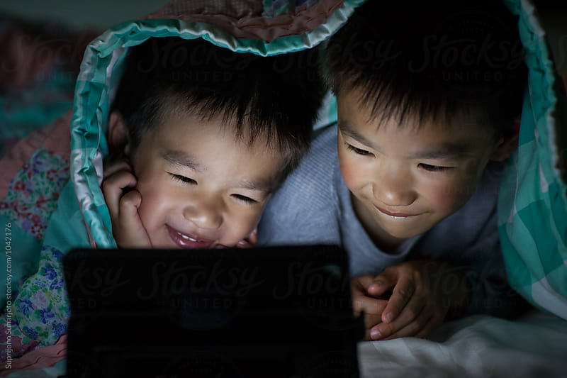 Asian kids watching on tablet computer in bed at home by Suprijono Suharjoto for Stocksy United