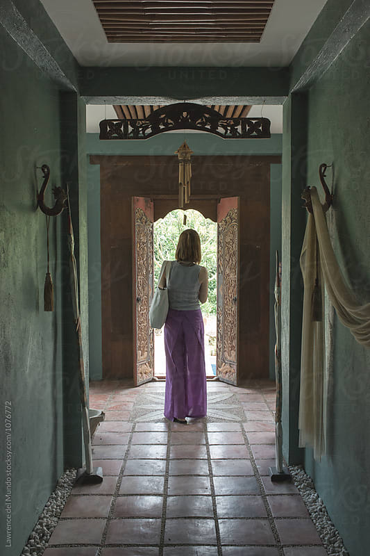 Woman standing at the end of the hallway and in front of a doorway.  by Lawrence del Mundo for Stocksy United