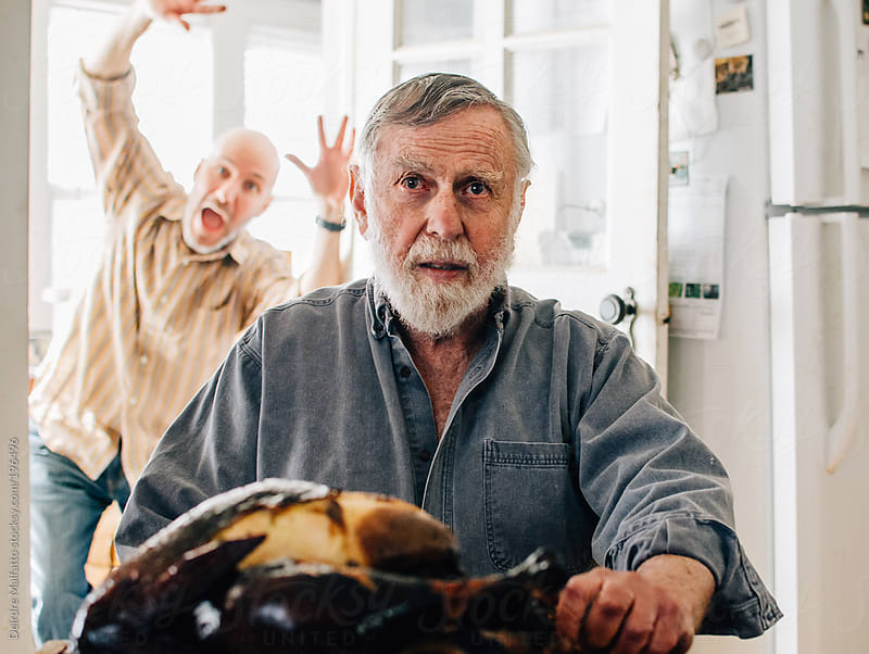 man photobombs another man who is carving a turkey by Deirdre Malfatto for Stocksy United